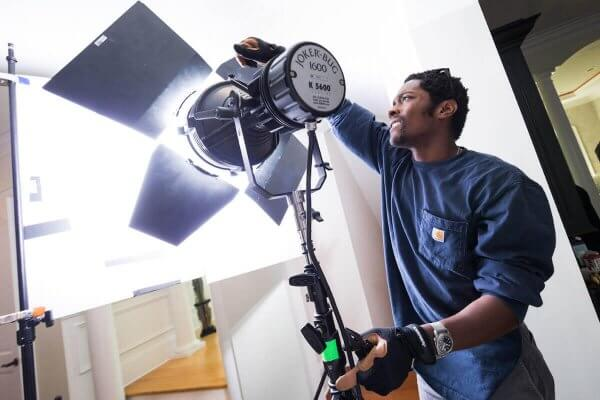 Shenandoah University student Orlando Levins adjusts lighting during a commercial feature film shoot.