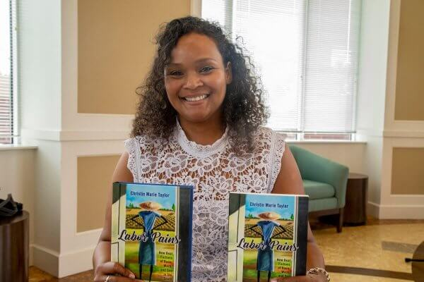 "Shenandoah University Assistant Professor of English Christin Taylor, Ph.D., with her book ""Labor Pains."""