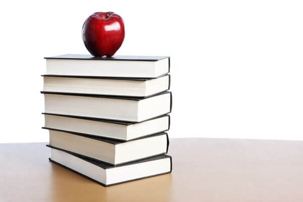 Stock photo of apple on top of books for story about Shenandoah education graduate student Sujin Chung winning VACTE scholarship.
