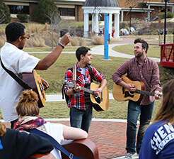 Students playing guitar outside